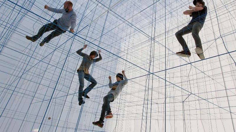 人を支えるほどの糸がグリッド状に張り巡らされた立体アート